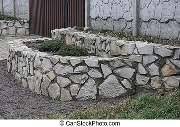 gray brown border of large stones and cobblestones outside on the ground