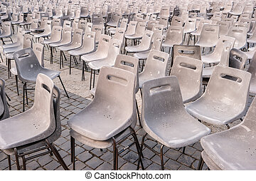 Gray chairs on pavement.