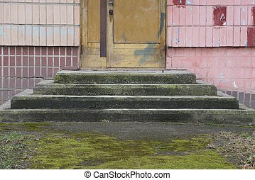 gray concrete threshold with old steps by the wooden door and wall with tiles