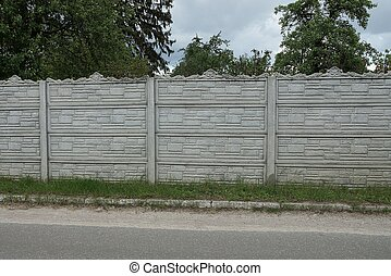 gray concrete wall of a fence on the street