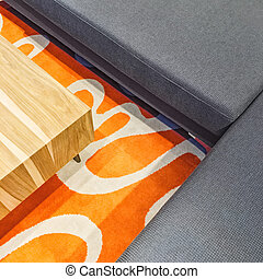 Gray corner sofa and orange carpet