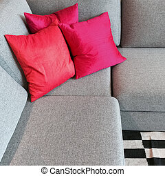 Gray corner sofa with silky red cushions