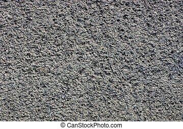 gray dark background of a stone porous wall