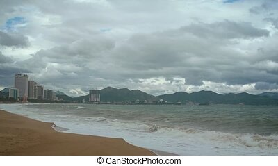 Heavy clouds mar the beautiful view of this popular, urban beach with the towers of Nha Trang, Vietnam in the background. 4k UltraHD video