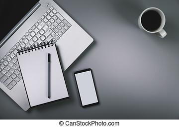 gray desk with laptop smartphone cup of coffee. top view with copy space