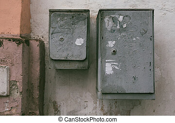 Gray electrical boxes on the background of an old multi-colored wall