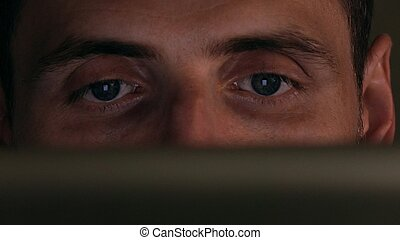 Gray eyes of focused intelligent young man using his tablet computer. Screen reflecting, device lighting glow
