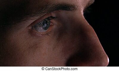 Gray eyes of intelligent young man using his tablet computer. Screen reflecting, device lighting glow
