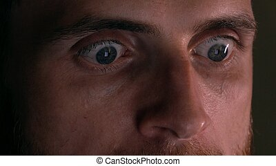 Gray eyes of surprised intelligent young man using his tablet PC. Screen reflecting, device lighting glow in the dark