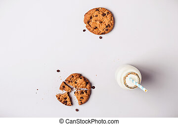 Background with chocolate chip cookies and bottle of milk