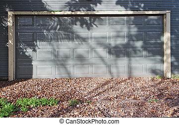 Gray garage door on similar color door during autumn with...
