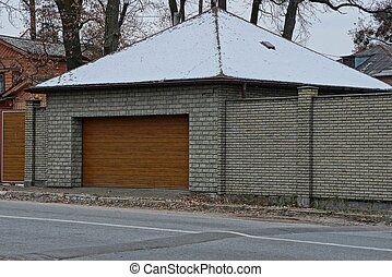 gray garage with brown gates and a brick fence outside in the snow