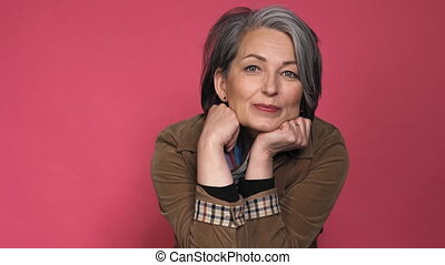 Gray-haired businesswoman smiles at camera. Beautiful woman in white shirt posing on dark pink background with text space. Prores 422.
