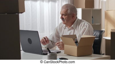 gray-haired man in a white shirt checks an order to be sent to a customer using a laptop. man sits at a work table in a warehouse of household chemicals.