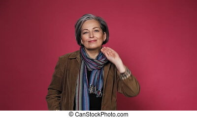 Gray-haired mature woman fixing her hair doing hairstyle. Creative Caucasian woman wearing casual clothes posing in studio on pink background. Prores 422.