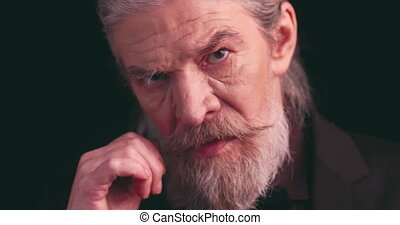Gray-haired stylish business elderly man in dark business clothes twists his mustache in a semi-lit room on a black background. Close up. Prores 422.