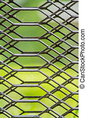 Gray iron mesh with a natural background.