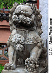 gray lion stone carving at the entrance of a temple