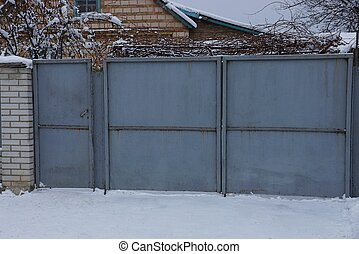 gray metal closed gate and part of the fence on the street in white snow