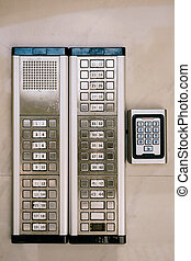 Gray metal intercom with buttons, apartment numbers and dialing numbers on the wall.