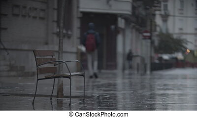 Street view with empty bench and some people walking under the rain. Dull day with nasty weather