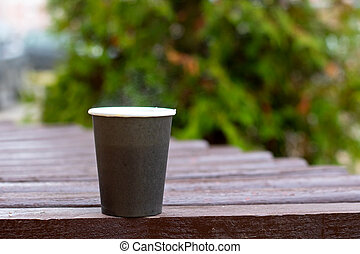 Gray plastic cup with coffee on the background of branches