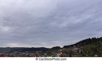 Gray rainy sky over small village on hillside. Time lapse -...