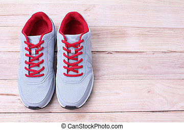 Gray sneakers running with red laces on a wooden background