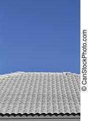 Gray tile roof against the blue sky