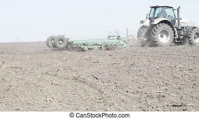 gray tractor go on black earth field