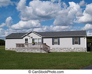 Gray Trailer Home with Stone Founda