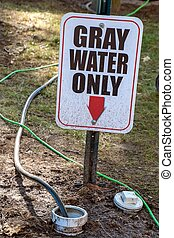 gray water warning sign on metal post in dirt with dirty hoses