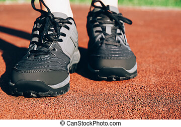 Gray woman sneakers on a sportsground close-up