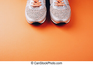 Gray woman sneakers on light peach background
