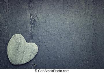 Gray zen heart shaped rock in the corner on a tile background