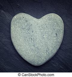 Gray zen heart shaped rock on a tile background