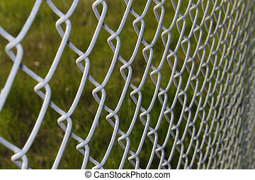 Grayish metal grid over green background