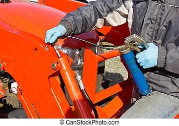 Greasing Tractor Piston - Hard at work maintaining piston...