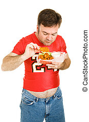 Greasy Chicken Wings - Overweight middle aged man eating...