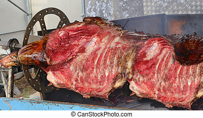 great beef cooked on a spit with the embers