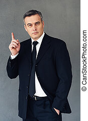Great business idea. Mature businessman gesturing and looking at camera while standing against grey background