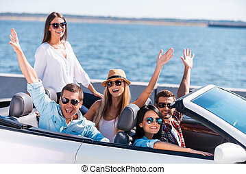 Great day for a ride. Group of young happy people enjoying road trip in their white convertible and raising their arms