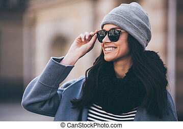 Great day for a walk. Portrait of beautiful young woman adjusting her sunglasses and looking away with smile while standing outdoors