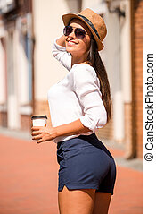Great day out. Beautiful young smiling woman in sunglasses adjusting her hat and looking over shoulder while walking by the street