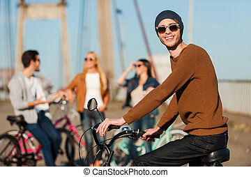 Great day with best friends. Handsome young man on bicycle looking at camera and smiling while his friends talking in the background