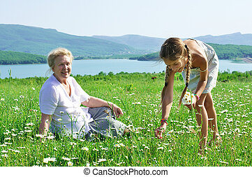 Great grandmother and great granddaughter in meadow - Great...
