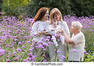 Great-grandmother, grandmother, mother holding a baby in a beautiful lavender field