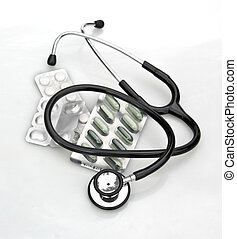 stethoscope and pills on white
