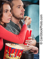 Great movie! Close-up of young couple feeding each other while watching movie at the cinema