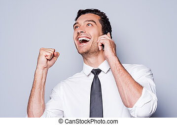 Great news! Happy young man in shirt and tie gesturing and smiling while talking on the mobile phone and standing against grey background
